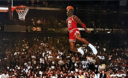 Michael Jordan voando no ar para encestar a bola
