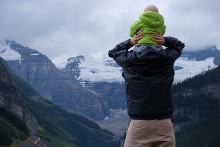 Pai com o filho às cavalitas, que observam as montnahs nevadas ao longe
