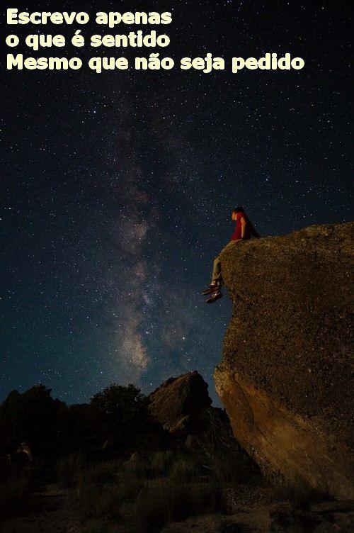jovem sentado à beira de um abismo contemplando as estrelas