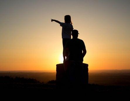 silhuetas de pai  e filha, em lugar alto ao poente que tudo inflama, a menina estende um braço apontando o horizonte