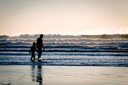 pai e filho entram num mar cheio de ondas espumejantes e baixinhas