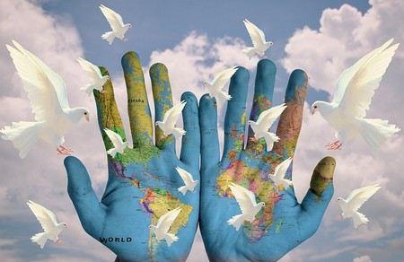 dua mãos abertas onde está pintado o mapa do mundo e rodeadas por pombas brancas