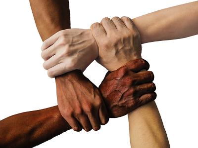quatro mãos unidas segurando-se mutuamente os pulsos