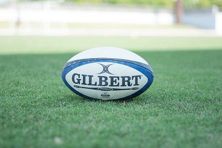 bola de rugby branca e azul sobre a relva