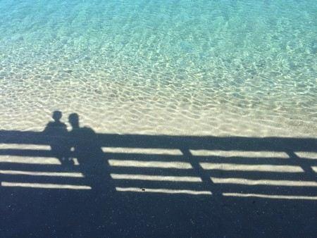 reflexo de pai e filho reclinados sobre cerca de madeira sobre o mar